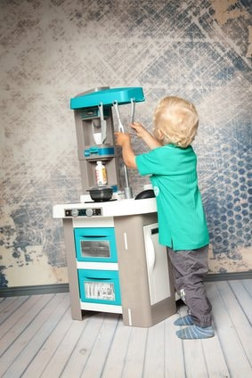 Junge spielt mit Tefal Kinderküche
